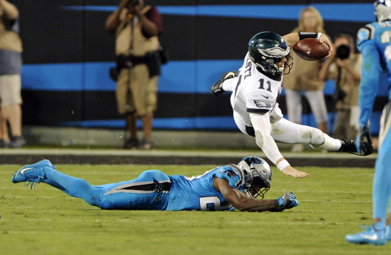 Philadelphia Eagles' Carson Wentz (11) is upended by Carolina Panthers' James Bradberry (24) in the second half of an NFL football game in Charlotte, N.C., Thursday, Oct. 12, 2017. (AP Photo/Mike McCarn)