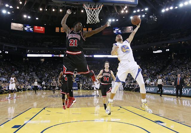 Golden State Warriors' Stephen Curry (30) scores past Chicago Bulls' Jimmy Butler (21) during the second half of an NBA basketball game on Thursday, Feb. 6, 2014, in Oakland, Calif. Golden State won 102-87. (AP Photo/Marcio Jose Sanchez)