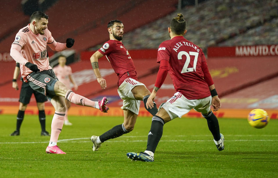 Sheffield United's Oliver Burke, left, scores his team's second goal during the English Premier League soccer match against Manchester United. (AP Photo/Tim Keeton,Pool)