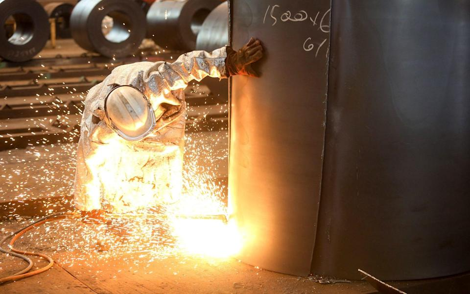 An employee cuts a sample from a roll of coiled steel inside Liberty House Group's rolling steel mill in Newport - Bloomberg