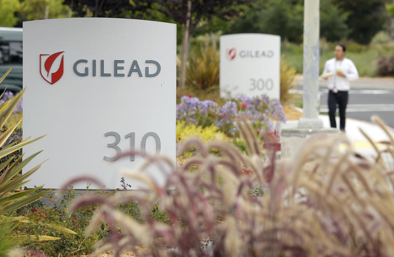 FILE - In this July 9, 2015, file photo, a man walks outside the headquarters of Gilead Sciences in Foster City, Calif. Gilead, thepharmaceutical giant that makes remdesivir,a promising coronavirus drug, has registered it as a rare disease treatment with U.S. regulators on Monday, March 23, 2020, a status that can potentially be worth millions in tax breaks and competition-free sales. (AP Photo/Eric Risberg, File)