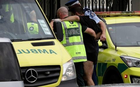Police and ambulance staff help a wounded man from outside a mosque in central Christchurch, New Zealand, Friday, March 15, 2019 - Credit: Mark Baker/AP