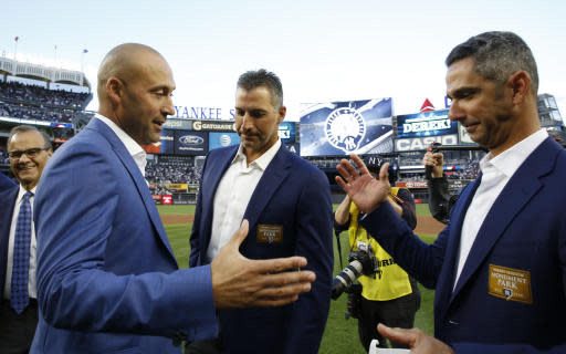 File-This May 14, 2017, file photo shows Rretired New York Yankees shortstop Derek Jeter, second from left, preparing to share hands with retired Yankees catcher Jorge Posada, far right, with another retired Yankee pitcher, Andy Pettitte, between them during an on-field, pregame ceremony retiring Jeter's number 2 at Yankee Stadium in New York. A person with knowledge of the negotiations says Posada has agreed to team up with Jeter again, this time in the front office of the Miami Marlins. The person says Posada will work as a special adviser to Jeter, his longtime New York Yankees teammate and now Marlins CEO. The person spoke to The Associated Press Tuesday, Feb. 12, 2019, on condition of anonymity because the hiring has not been formally announced. (AP Photo/Kathy Willens, File)