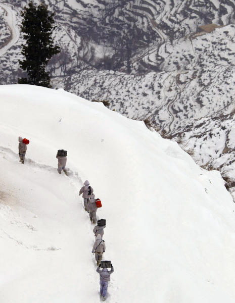 In this Sunday, Feb. 19, 2012 photo, Pakistani Army soldiers with the 20th Lancers Armored Regiment carry supplies up the 8000-foot mountain near their outpost, Kalpani Base, in Pakistan's Dir province on the Pakistan-Afghan border. Kalpani is on the front line in the 10-year war against militant Islamists, a war which allies Pakistan with the U.S. and NATO in an uneasy, distrustful partnership. Pakistan feels scapegoated for the coalition's failures in Afghanistan. At the same time it's accused of playing a double game, fighting the militants it chooses to fight while giving others safe havens and logistical support for their actions in Afghanistan. (AP Photo/Anja Niedringhaus)