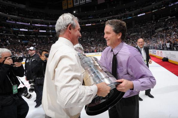 LOS ANGELES, CA - JUNE 13: Darryl Sutter of the Los Angeles Kings hands the Stanley Cup Trophy over to general manager Dean Lombardi after defeating the New York Rangers in the second overtime period of Game Five of the 2014 NHL Stanley Cup Final at Staples Center on June 13, 2014 in Los Angeles, California. (Photo by Andrew D. Bernstein/NHLI via Getty Images)