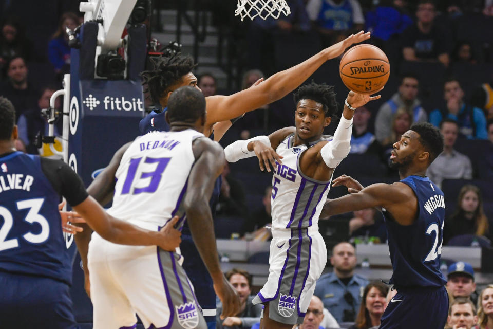 Sacramento Kings guard De'Aaron Fox(5) passes the ball to Kings center DeWayne Dedmon (13) as Minnesota Timberwolves center Karl-Anthony Townstries to block the pass and Timberwolves forward Andrew Wiggins, right, looks on during the first half of an NBA basketball game Monday, Jan. 27, 2020, in Minneapolis. (AP Photo/Craig Lassig)