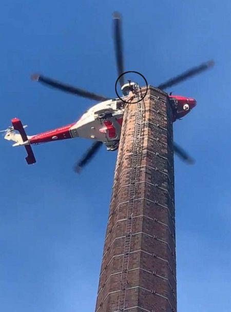 PHOTO: A man dangles from 290 foot smoke stack as an emergency helicopter tries to get close enough to rescue him in northern England. (Naim Asghar via Storyful)