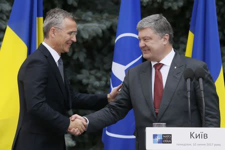 NATO Secretary General Jens Stoltenberg and Ukrainian President Petro Poroshenko shake hands during a joint news conference following a meeting of the NATO-Ukraine Commission in Kiev, Ukraine, July 10, 2017. REUTERS/Valentyn Ogirenko
