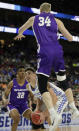 Kentucky's Reid Travis, center, looks for a shot as Abilene Christian's Kolton Kohl (34) jumps high to defend during the first half of a first-round game in the NCAA mens college basketball tournament in Jacksonville, Fla. Thursday, March 21, 2019. (AP Photo/John Raoux)