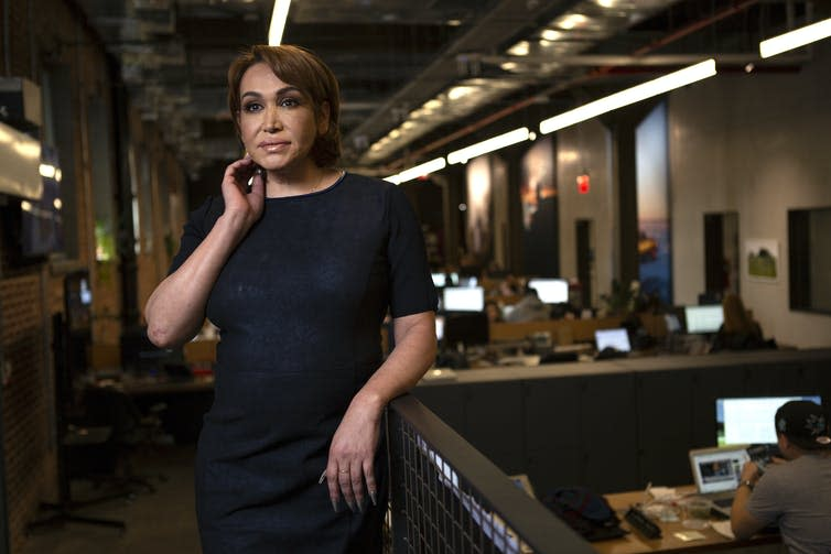 A transgender woman stands in business attire in an office