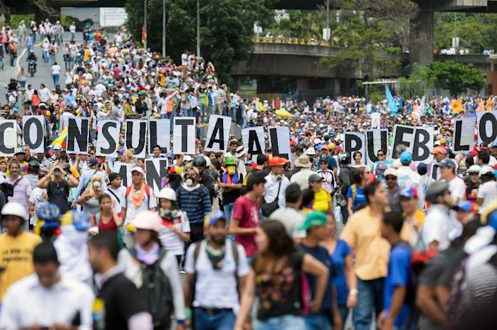 "Opposition activists hold signs spelling the phrase, ""Consult with the people"" during a protest against the government of Nicolas Maduro in Caracas on May 31, 2017 (AFP Photo/FEDERICO PARRA)"