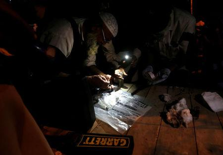 Security officials collect evidence from the site of a a drive-by bomb attack at a Shi'ite mosque, at hospital in Karachi, Pakistan, October 17, 2016. REUTERS/Akhtar Soomro