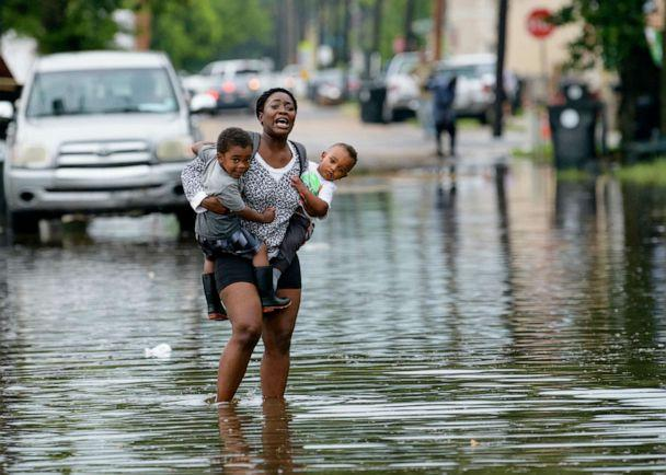 PHOTO: A woman carries two children through rising waters in New Orleans, July 10, 2019, during flooding from a storm in the Gulf Mexico. (Matthew Hinton/AP)