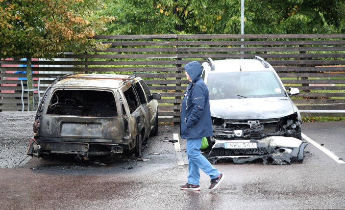 """A person walks past burned cars parked at Frolunda Square in Gothenburg, Tuesday, Aug. 14, 2018. Masked youth torched dozens of cars overnight in Sweden and threw rocks at police, prompting an angry response from the prime minister, who on Tuesday spoke of an """"extremely organized"""" night of vandalism. (Adam Ihse/TT via AP)"""