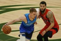 Milwaukee Bucks' Donte DiVincenzo tries to drive past Toronto Raptors' Fred VanVleet during the first half of an NBA basketball game Thursday, Feb. 18, 2021, in Milwaukee. (AP Photo/Morry Gash)