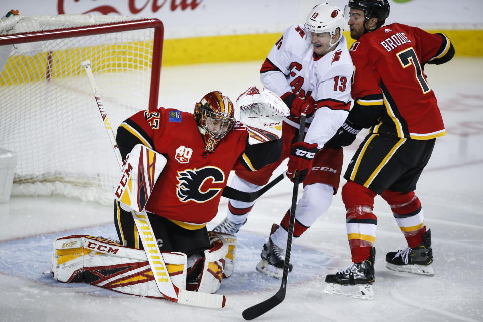 Carolina Hurricanes' Warren Foegele, center, gets caught between Calgary Flames goalie David Rittich, left, and Flames' T. J. Brodie during second-period NHL hockey game action in Calgary, Alberta, Saturday, Dec. 14, 2019. (Jeff McIntosh/The Canadian Press via AP)