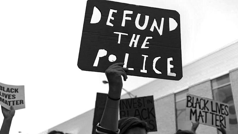 """Protesters carry a """"Defund the Police"""" sign on West Division Street during the March of Justice from Union Park to Cabrini-Green on Saturday, June 6, 2020 in Chicago to demand police accountability. (Brian Cassella/Chicago Tribune/Tribune News Service via Getty Images)"""
