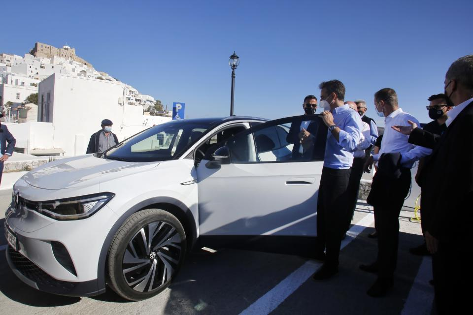 Greek Prime Minister Kyriakos Mitsotakis opens the door of an electric car as he accompanied by Volkswagen Group CEO Herbert Diess during the official launch of a project to introduce and test electric vehicles and sustainable energy systems on the Aegean Sea island of Astypalea, Greece,on Wednesday, June 2, 2021. The government has partnered with the German carmaker on the island project aimed a switching to electric vehicle use over the next five years. (Alexandros Vlachos/Pool via AP)