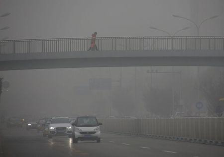A pedestrian walks on a bridge on an extremely polluted day as hazardous, choking smog continues to blanket Beijing, China December 1, 2015. REUTERS/Kim Kyung-Hoon