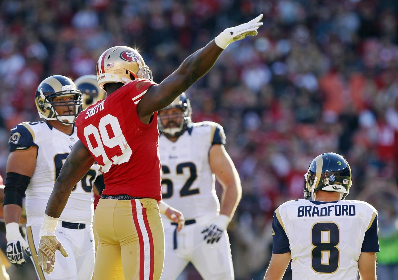 SAN FRANCISCO, CA - NOVEMBER 11: Linebacker Aldon Smith #99 of the San Francisco 49ers salutes the crowd on Veteran's Day after sacking quarterback Sam Bradford #8 of St. Louis Rams in the second quarter on November 11, 2012 at Candlestick Park in San Francisco, California.  The teams tied 24-24 in overtime.  (Photo by Brian Bahr/Getty Images)