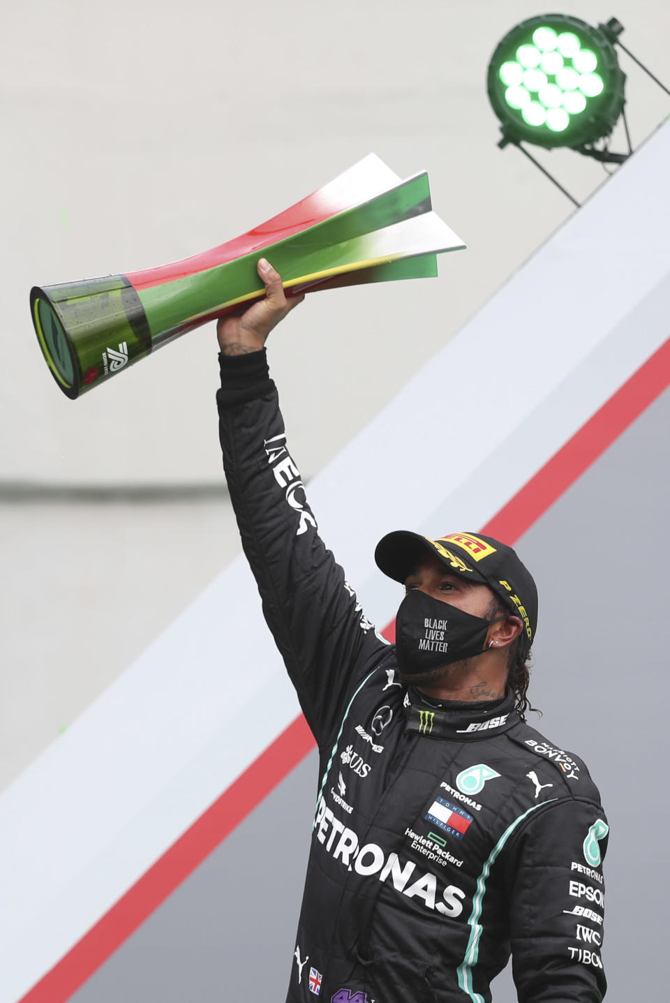 Mercedes driver Lewis Hamilton of Britain holds his trophy on the podium after his record breaking win during the Formula One Portuguese Grand Prix at the Algarve International Circuit in Portimao, Portugal, Sunday, Oct. 25, 2020. (Jose Sena Goulao, Pool via AP)