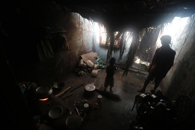 A man and his son stand inside their damaged house after Cyclone Phailin hit Gopalpur village
