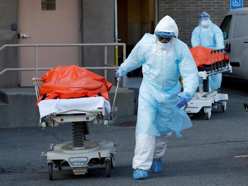 """Healthcare workers wheel the bodies of deceased people from the Wyckoff Heights Medical Center during the coronavirus outbreak in Brooklyn, New York City, April 4, 2020. <p class=""""copyright"""">Andrew Kelly/Reuters</p>"""