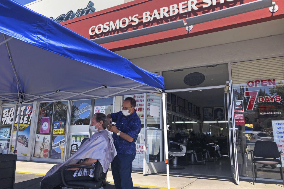 FILE - In this July 22, 2020 file photo, a customer of Cosmo's barber shop receives a haircut in the parking lot in front of the shop in Pleasanton, Calif. The coronavirus and the drastic measures put in place by government officials to try to control its spread had a severe toll on many small businesses in the U.S. Restaurants, hair salons, event planners and other businesses that rely on people being in close proximity were particularly hard-hit, as were those tied to tourism. (AP Photo/Ben Margot)