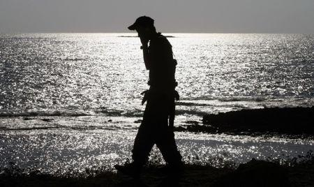 Israeli soldier speaks on mobile phone while walking alongside beach near Nahariya