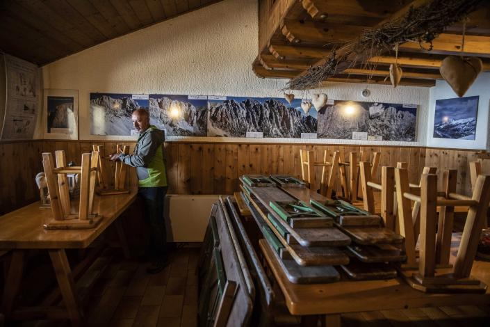 In this image take on Friday, April 24, 2020 Claudio Trentani, 57, moves stools inside his shelter 'Baita Cassinelli', at 1568mt, at the foot of Mt. Presolana, in Castione della Presolana, near Bergamo, northern Italy. On Saturday, March 7, 2020, a day before the national lockdown was announced, he had over 100 people for lunch and was sincerely worried about the risks of infection. Now he is waiting to see if he can reopen under new laws applicable to restaurants, but with his indoor area of about 60 mq he is hoping to make the most of his outdoor space. (AP Photo/Luca Bruno),