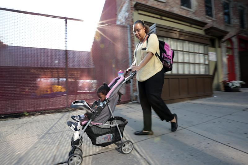 Ke'sha Scrivner, right, heads to a subway Metro stop after picking up her daughter Ka'Lani Scrivner, 1, from day care, Tuesday, July 9, 2013, in Washington. Once on welfare, Scrivner worked her way off by studying early childhood education and landing a full-time job for the District of Columbia's education superintendent. She sees education as the path to a better life for herself and all five of her children, pushing them to finish high school and continue with college or a trade school. (AP Photo/Alex Brandon)