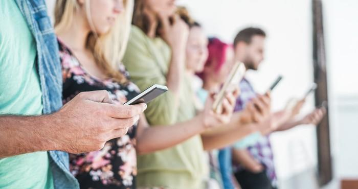 A group of people standing and using their smartphones.