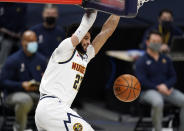 Denver Nuggets guard Jamal Murray hangs from the rim after dunking against the Utah Jazz in the second half of an NBA basketball game Sunday, Jan. 31, 2021, in Denver. (AP Photo/David Zalubowski)