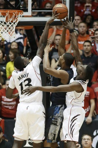 Cincinnati center Cheikh Mbodj (13) blocks a shot by Georgetown forward Mikael Hopkins in the first half of an NCAA college basketball game, Friday, Feb. 15, 2013, in Cincinnati. Cincinnati forward Justin Jackson helps out at right. (AP Photo/Al Behrman)