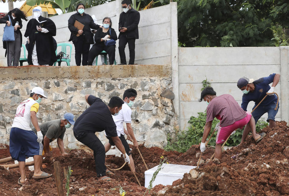 Workers bury a man as family members watch in the special section of the Jombang cemetery opened to accommodate the surge in deaths during coronavirus outbreak in Tangerang, Indonesia, Tuesday, Jan. 26, 2021. Indonesia has reported more cases of the virus than any other countries in Southeast Asia. (AP Photo/Tatan Syuflana)