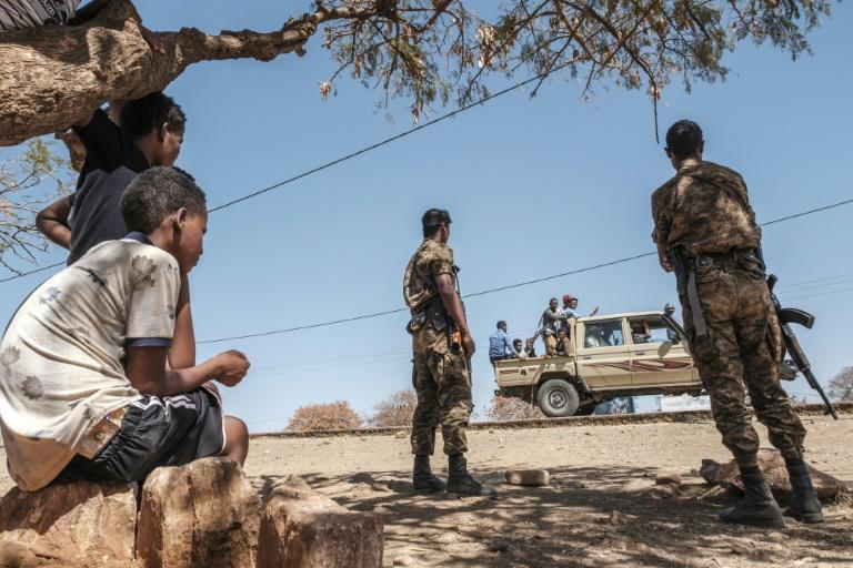 Ethiopian troops watch as a pick-up truck with militia men passes by the camp