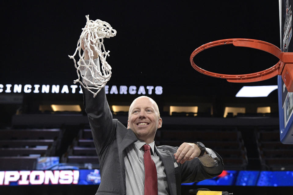 Cincinnati head coach Mick Cronin holds the net toward fans in the stands after cutting it down following a win over Houston in an NCAA college basketball championship game at the American Athletic Conference tournament Sunday, March 11, 2018, in Orlando, Fla. (AP Photo/Phelan M. Ebenhack)