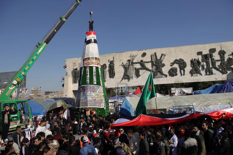 Demonstrators work to install a Christmas tree, with posters of protesters who have been killed in demonstrations and their belongings, while anti-government protesters hold a national flag during a sit-in at Tahrir Square in Baghdad, Iraq, Tuesday, Dec. 24, 2019. (AP Photo/Khalid Mohammed)
