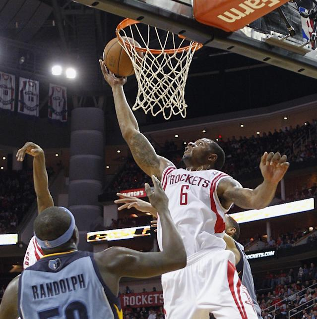Houston Rockets forward Terrence Jones (6) tips in an offensive rebound as Memphis Grizzlies forward Zach Randolph (50) watches during the second half of an NBA basketball game Thursday, Dec. 26, 2013, in Houston. The Rockets won 100-92. (AP Photo/Bob Levey)