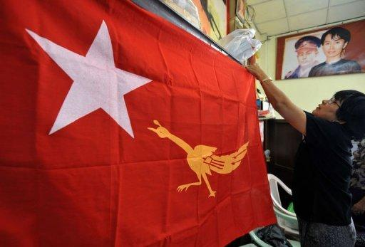 Members of Myanmar's opposition National League for Democracy (NLD) show their new emblem on a party flag at the NLD headquarters in Yangon on December 12, 2011. Myanmar authorities have given the green light to Aung San Suu Kyi's opposition to rejoin mainstream politics, setting the scene for the Nobel laureate to run for a seat in the new parliament