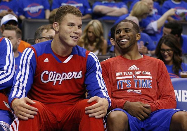 Los Angeles Clippers guard Chris Paul, right, laughs with teammate Blake Griffin, left, as they sit on the bench in the fourth quarter of Game 1 of the Western Conference semifinal NBA basketball playoff series in Oklahoma City, Monday, May 5, 2014. Los Angeles won 122-105. (AP Photo/Sue Ogrocki)
