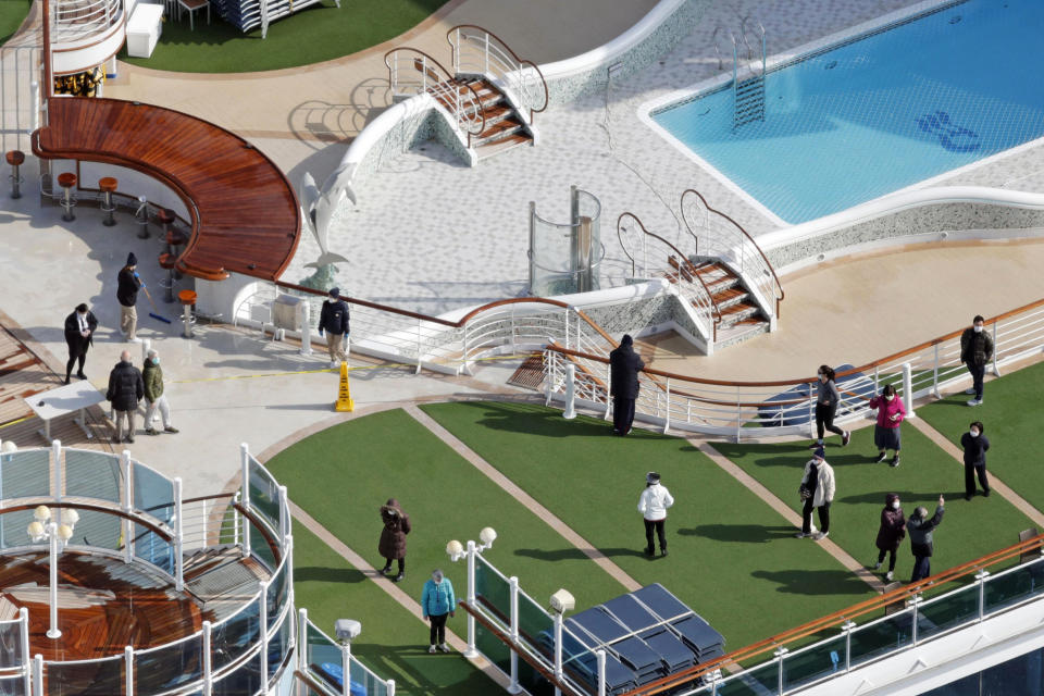 Masked passengers are seen on the deck of the cruise ship Diamond Princess docked at Yokohama Port, near Tokyo, Friday, Feb. 7, 2020. Japan on Friday reported 41 new cases of a virus on the cruise ship that's been quarantined. About 3,700 people have been confined aboard the ship. (Sadayuki Goto/Kyodo News via AP)