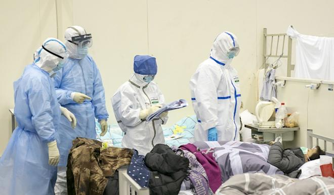 Medical staff check on a patient at a temporary hospital in Wuhan. Photo: Xinhua