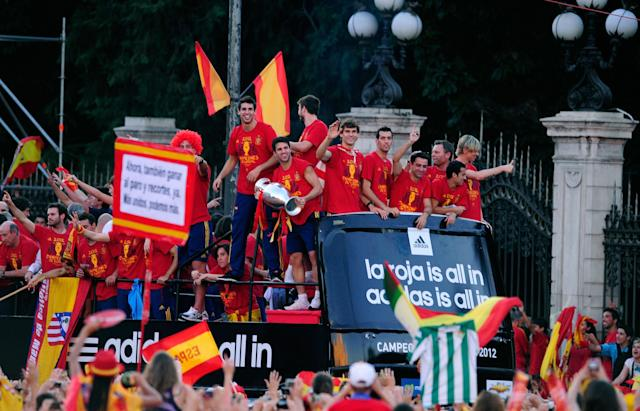 MADRID, SPAIN - JULY 02: Cesc Fabregas of Spain holds the UEFA EURO 2012 trophy while celebrating with fellow players as they parade the UEFA EURO 2012 trophy on a double-decker bus on July 2, 2012 in Madrid, Spain. Spain beat Italy 4-0 in the UEFA EURO 2012 final match in Kiev, Ukraine, on July 1, 2012. (Photo by Denis Doyle/Getty Images)
