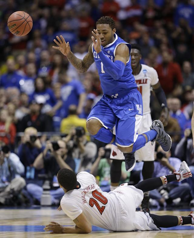 Kentucky's James Young (1) leaps over Louisville's Wayne Blackshear (20) as he passes the ball during the first half of an NCAA Midwest Regional semifinal college basketball tournament game Friday, March 28, 2014, in Indianapolis. (AP Photo/David J. Phillip)