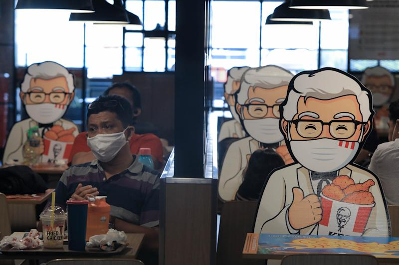 A customer sits next to a Colonel Sanders' character mounted at a table as a way of maintaining the social distance, a precaution against the spread of coronavirus (covid-19) at KFC. (Photo by Jovan Triniti / SOPA Images/Sipa USA)