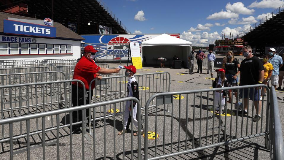 A young fan has his temperature checked during a walkthrough at the New Hampshire Motor Speedway Friday, July 31, 2020, in Loudon, N.H., in preparation for this Sunday's Foxwoods 301 NASCAR auto race. (AP Photo/Charles Krupa)