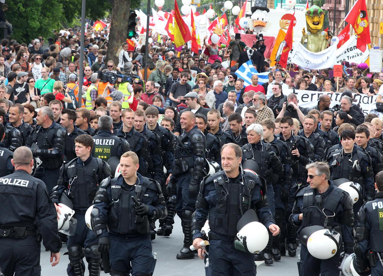 German police officers escort an anti-capitalism protest march with some 20,000 people in Frankfurt, Germany, Saturday, May 19, 2012. Protesters peacefully filled the city center of continental Europe's biggest financial hub in their protest against the dominance of banks and what they perceive to be untamed capitalism, Frankfurt police spokesman Ruediger Regis said. The protest group calling itself Blockupy has called for blocking the access to the European Central Bank, which is located in Frankfurt's business district. (AP Photo/Michael Probst)