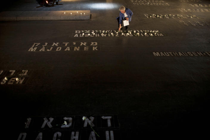 A relative of Holocaust victims lays flowers next to names of concentration camps during a ceremony marking the annual Holocaust Remembrance Day at the Yad Vashem Holocaust Memorial in Jerusalem, Monday, April 8, 2013. Israel came to a standstill for two mournful minutes Monday as sirens pierced the air in an annual ritual to remember the 6 million Jews systematically murdered by German Nazis and their collaborators during the Holocaust in World War II. (AP Photo/Oded Balilty)