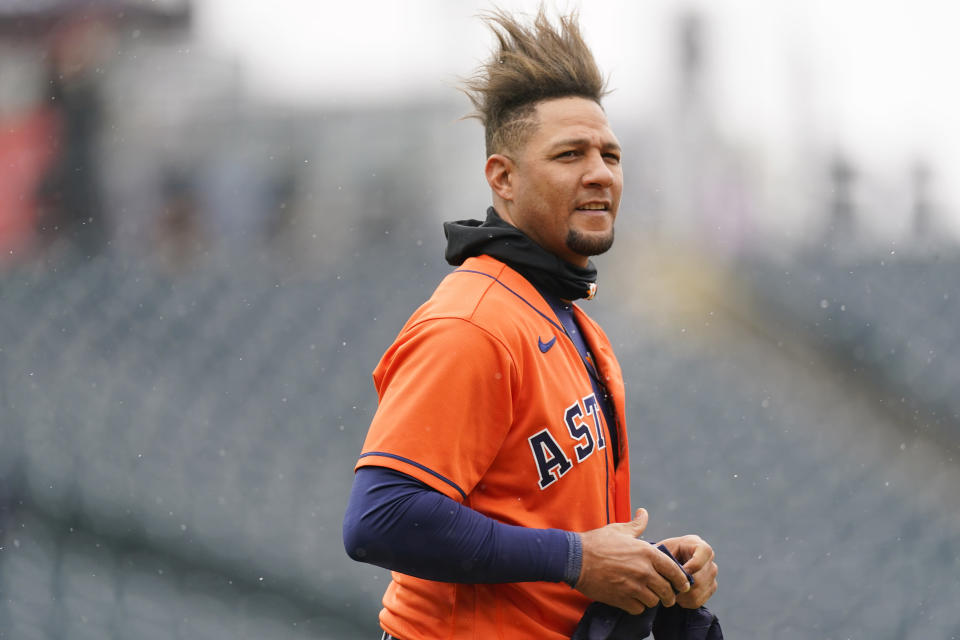 Houston Astros first baseman Yuli Gurriel waits for his hat and glove after flying out against Colorado Rockies starting pitcher Austin Gomber to end the top of the fourth inning of a baseball game Wednesday, April 21, 2021, in Denver. (AP Photo/David Zalubowski)